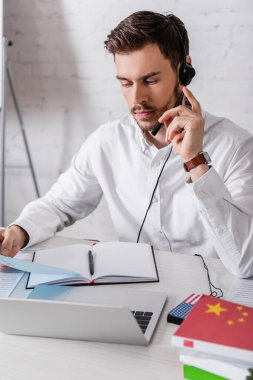 Young interpreter in headset holding document near digital translator and dictionaries on blurred foreground stock vector