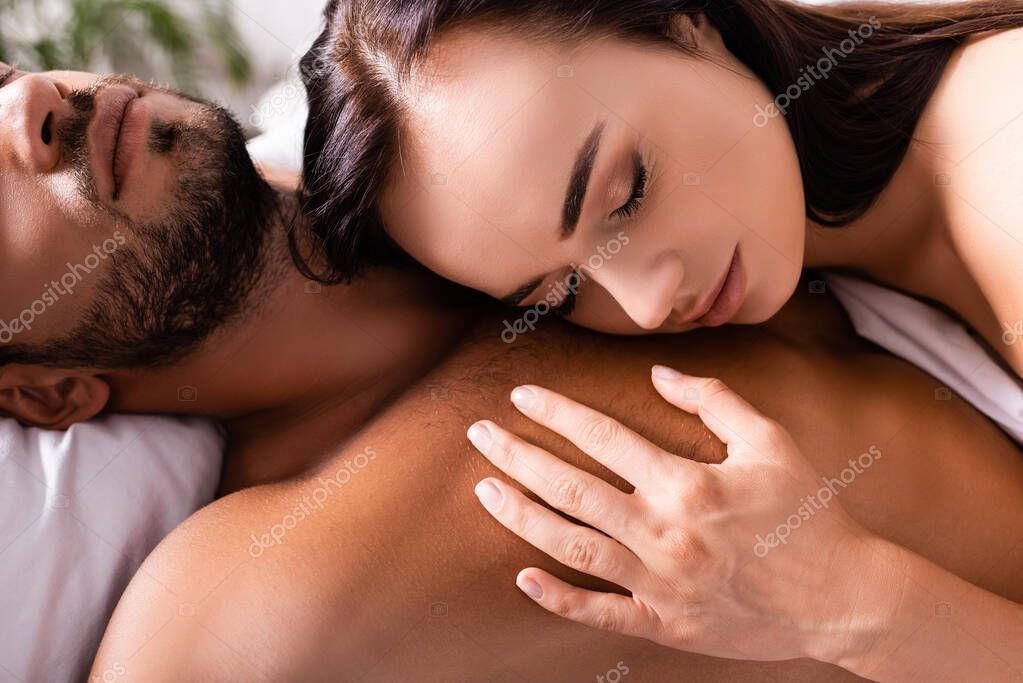 Close up view of young woman with closed eyes leaning on chest of boyfriend in bedroom on blurred background stock vector