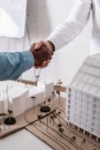 ostříhaný pohled na mezirasové obchodní partnery potřesení rukou v blízkosti modelů budov a alternativní elektrárny