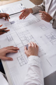 cropped view of businesswoman pointing with hand at blueprint near multiethnic business partners
