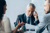Mature investor looking at documents while business people with smartphone talking on blurred foreground