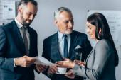 Mosolygó üzletasszony vízzel rámutatva papír közel befektető csésze és kolléga dokumentummal az irodában