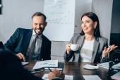 Veselí podnikatelé s kávou mluvit s poradcem na rozmazané popředí u papírů na stole