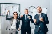 Lächelnde Geschäftsleute zeigen Yah-Geste in die Kamera in der Nähe von Flipchart im Büro