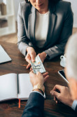 Investor giving dollars to businesswoman on blurred background in office