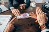 Oříznutý pohled na obchodníky ukazující stop gesto a ukazující na eurobankovky poblíž kolegy a papíry na rozmazaném popředí