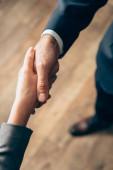 Ořezaný pohled na podnikatele potřásání rukou v kanceláři