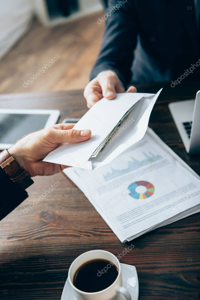 Cropped view of investor on blurred background giving envelope with money to businessman near papers and cup of coffee stock vector