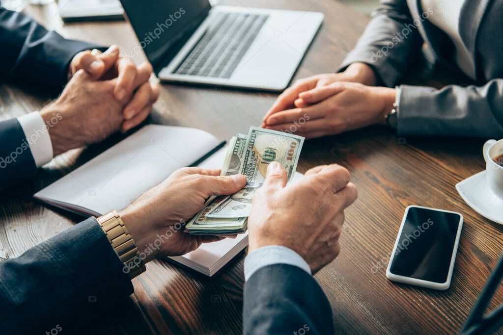 Cropped view of businessman holding money near smartphone, coffee and colleagues on blurred background stock vector