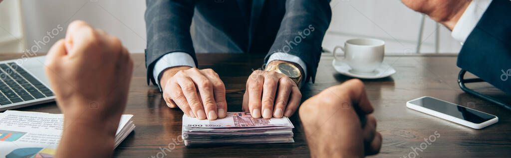 Cropped view of investor holding euro banknotes near papers and businesspeople showing yeah gesture on blurred foreground, banner stock vector