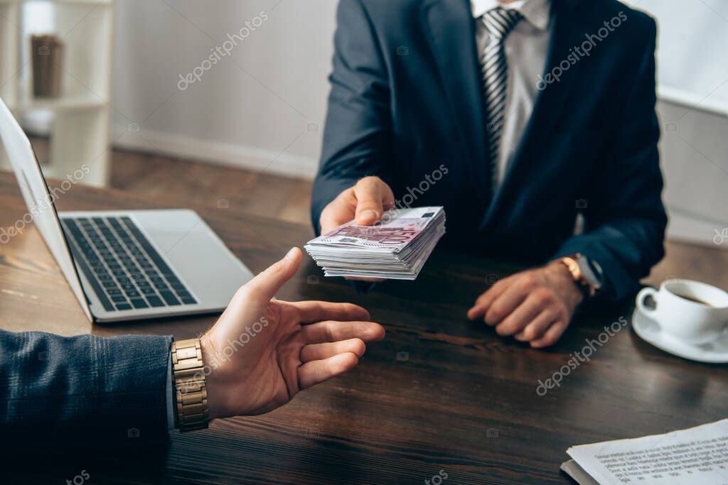 Cropped view of businessman taking money from investor near laptop and papers on blurred background stock vector