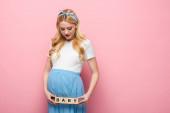 blondýny mladá těhotná žena drží kostky s baby písmem na růžovém pozadí