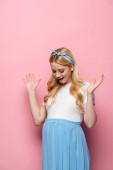 überrascht blonde junge schwangere Frau auf rosa Hintergrund