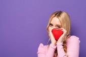 szőke fiatal nő gazdaság piros szív alakú doboz közel arc lila háttér
