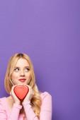 álmodozó szőke fiatal nő gazdaság piros szív alakú doboz lila háttér