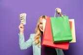 Lächelnde blonde junge Frau im modischen türkisfarbenen Blazer mit Einkaufstaschen und Geld auf lila Hintergrund