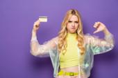 smutné blondýny mladá žena v barevné oblečení ukazující kreditní karty a palec dolů na fialovém pozadí