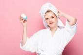 mladá žena v županu s ručníkem na hlavě drží deodorant na růžové