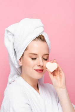 Young woman in bathrobe with closed eyes, towel on head and facial heart shaped sponge isolated on pink stock vector