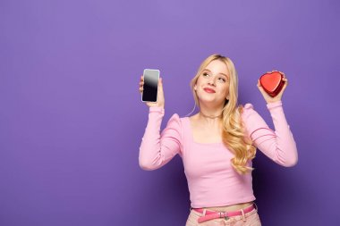 Blonde young woman with red heart shaped box and smartphone on purple background stock vector