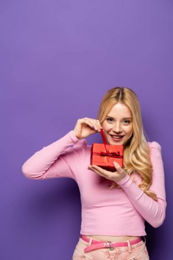 Happy blonde young woman opening red gift box on purple background stock vector