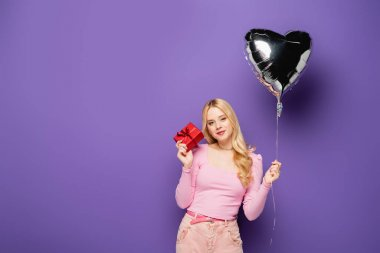 Blonde young woman holding heart shaped balloon and gift on purple background stock vector