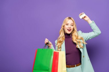 Happy blonde young woman in fashionable turquoise blazer with shopping bags and credit card on purple background stock vector
