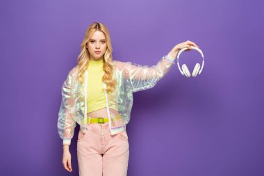 Sad blonde young woman in colorful outfit holding headphones on purple background stock vector