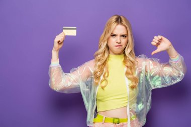Sad blonde young woman in colorful outfit showing credit card and thumb down on purple background stock vector
