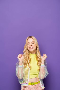 Happy blonde young woman in colorful outfit with closed eyes on purple background stock vector