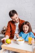 izgatott lány eszik kukoricapehely közelében apa gazdaság alma a kórházban