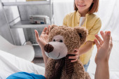 cropped view of smiling child holding teddy bear near father in hospital