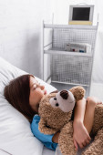 sick, upset girl hugging teddy bear while lying in bed in hospital