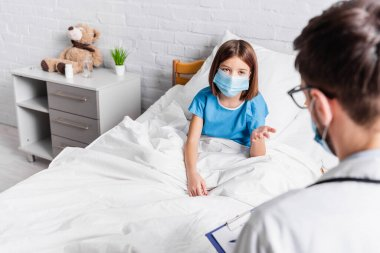 Child in medical mask pointing with hand while talking to doctor on blurred foreground stock vector