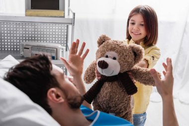 Smiling girl giving teddy bear to father lying in hospital stock vector