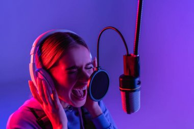 Woman in wireless headphones recording song while singing in microphone on purple stock vector