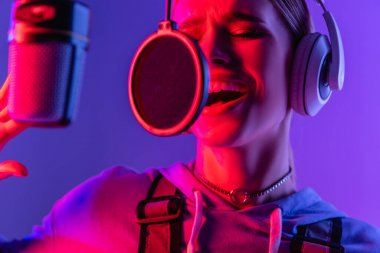 young singer in wireless headphones recording song while singing in microphone on purple with color filter