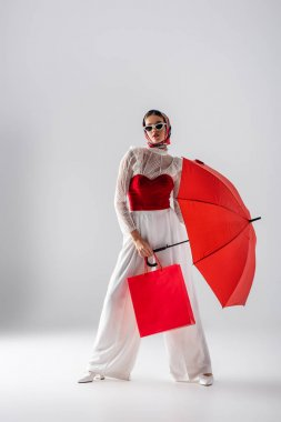 Full length of fashionable woman in headscarf and sunglasses holding red umbrella and shopping bag while posing on white stock vector