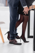 partial view of businessman seducing secretary in high heeled shoes in office