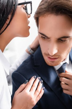 Passionate businesswoman whispering in ear of colleague while flirting in office stock vector