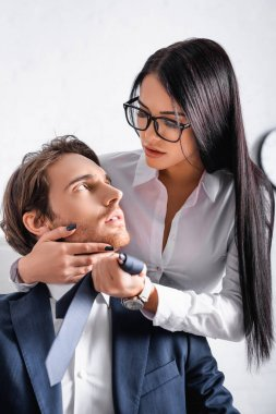 Sensual brunette businesswoman touching face of colleague while seducing him in office stock vector