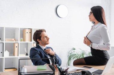 Brunette secretary seducing businessman while unbuttoning blouse on desk in office stock vector