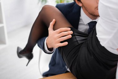 Partial view of businessman hugging leg of seductive secretary sitting on desk stock vector
