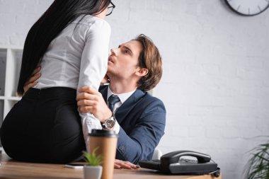 Passionate businessman hugging seductive businesswoman sitting on desk, blurred foreground stock vector