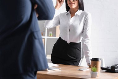 Cropped view of smiling, sexy businesswoman seducing colleague in office, blurred foreground stock vector