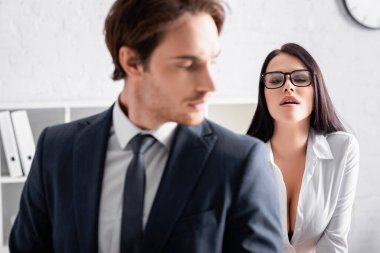 Sexy brunette businesswoman in eyeglasses seducing young colleague on blurred foreground stock vector