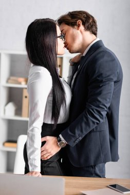 Young manager kissing seductive brunette businesswoman while standing in office stock vector