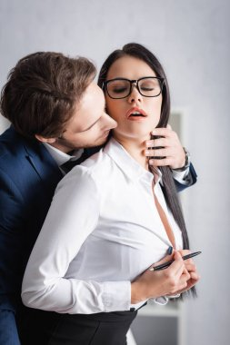 Passionate businesswoman unbuttoning blouse while young colleague seducing her in office stock vector