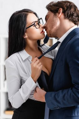 Sexy businesswoman pulling tie of young businessman while seducing him in office stock vector