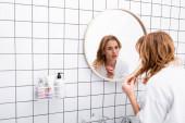 ustaraná žena v županu úpravy vlasů při pohledu na zrcadlo v koupelně